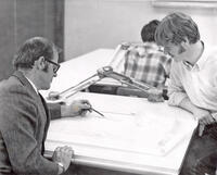 Instructor drafting plans at drafting table while student observes