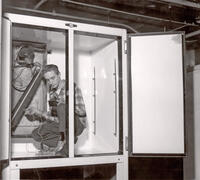 Douglas Brienholt using electric thermometer in refrigeration unit