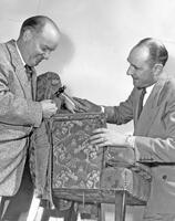 Cecil Samuelson and Jay L. Nelson holding an upholstered chair, early 1952