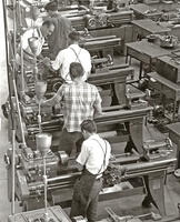 Students operating metal lathe machines as instructor observes, circa 1956-1957