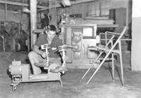 Student observing the operation of a motorized cycle, circa early 1960s
