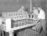 Fritz A. Barthel, Vernon E. Brundage, and Lyle J. Hull tying springs in the process of building a couch, 1952