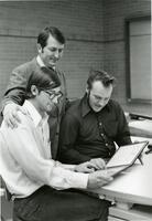 An Instructor Presenting two Students their Diplomas
