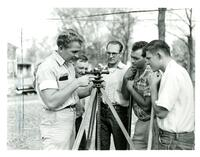 Individuals using surveying instrument to survey the site for student project house, 1954