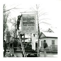 Installation of a street sign at student project house site, 1954