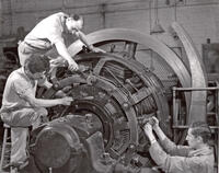 Clyde Fritch, Charles Moody, and Keith Hales working on large DC generator, circa 1956-1957
